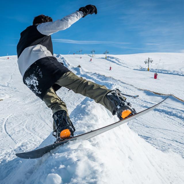 """Snowboarder sliding against blue sky"" stock image"