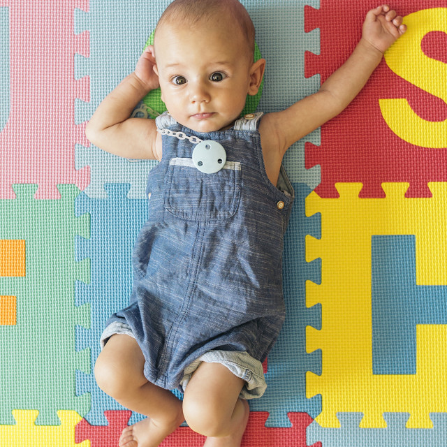 """""""Cute surprised baby in overall on colorful background"""" stock image"""