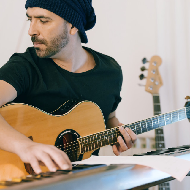 """Man Recording Guitars and piano at his Home Sound Studio."" stock image"