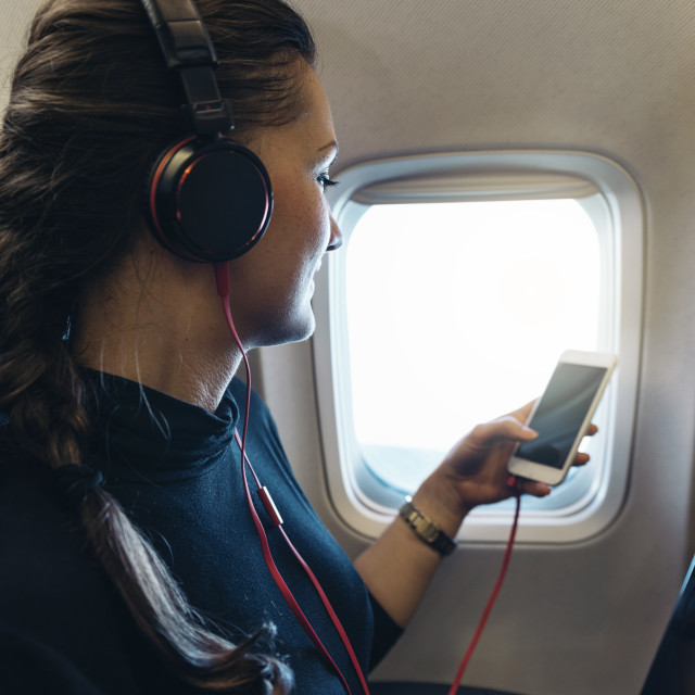 """Woman using smartphone on cabin of airplane."" stock image"