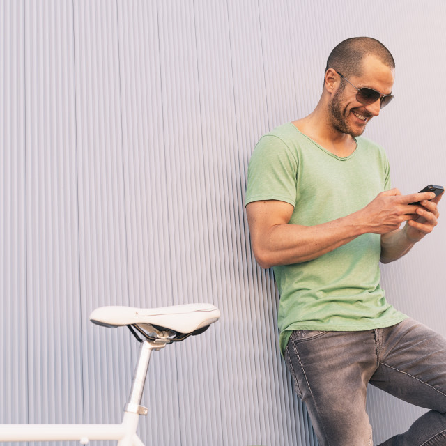 """Handsome young man with mobile phone and fixed gear bicycle."" stock image"