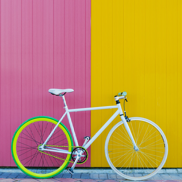 """City bicycle fixed gear on yellow and red wall. Cycling or commuting in city..."" stock image"