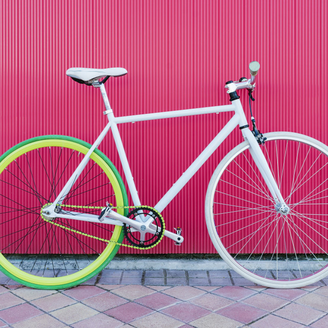 """City bicycle fixed gear on red wall."" stock image"