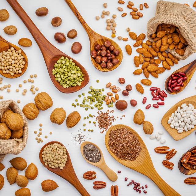 """""""Various legumes and different kinds of nuts in spoons. Walnuts kernels..."""" stock image"""