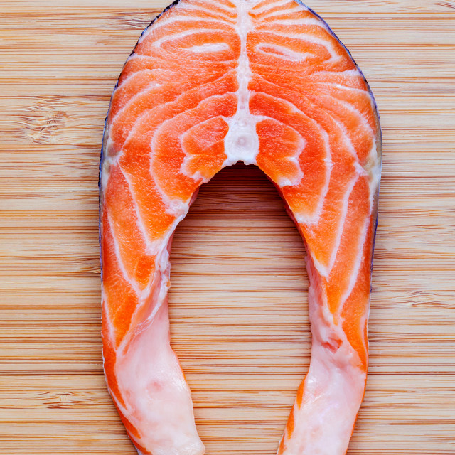 """Fresh salmon fillet sliced flat lay on bamboo cutting board. Fresh salmon..."" stock image"