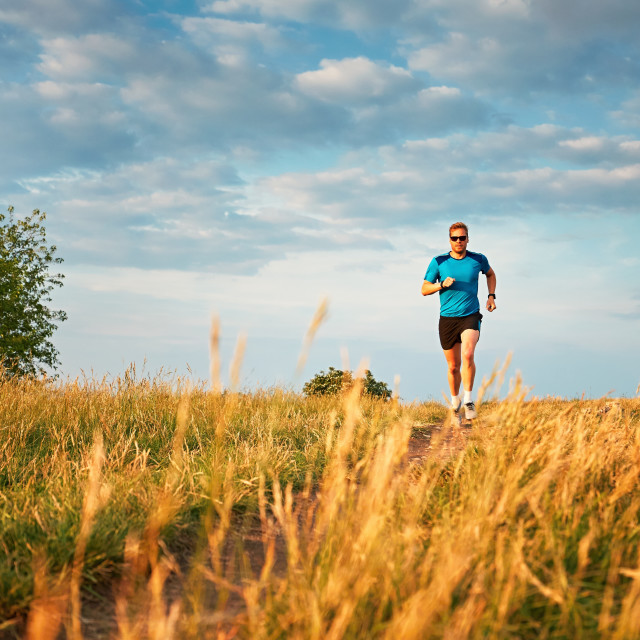 """Athletic runner on the hillside"" stock image"