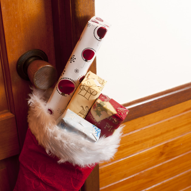 """Red Christmas stocking filled with Santa gifts"" stock image"