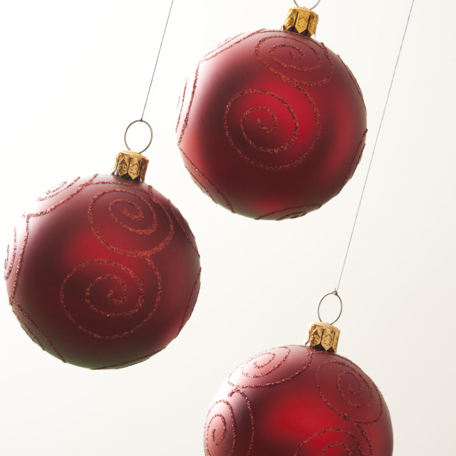 """Three red Christmas balls hanging on white background"" stock image"