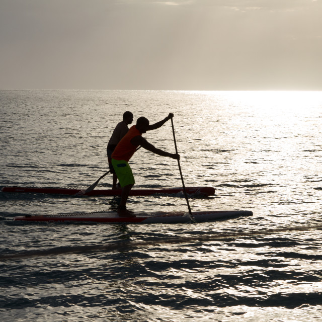 """Two Paddleboarders as the sun is setting"" stock image"