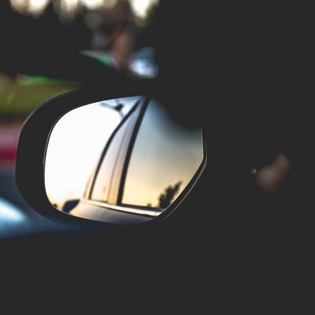 """Exterior rearview mirror in car with sunset reflection"" stock image"
