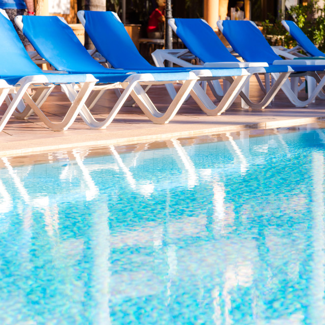 """Blue deck chairs arranged around the pool"" stock image"