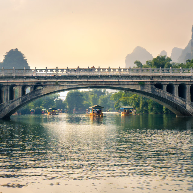 """YANGSHUO, CHINA - SEPTEMBER 23, 2016: Boats with tourists floating on Li River, below a stone bridge at sunset"" stock image"