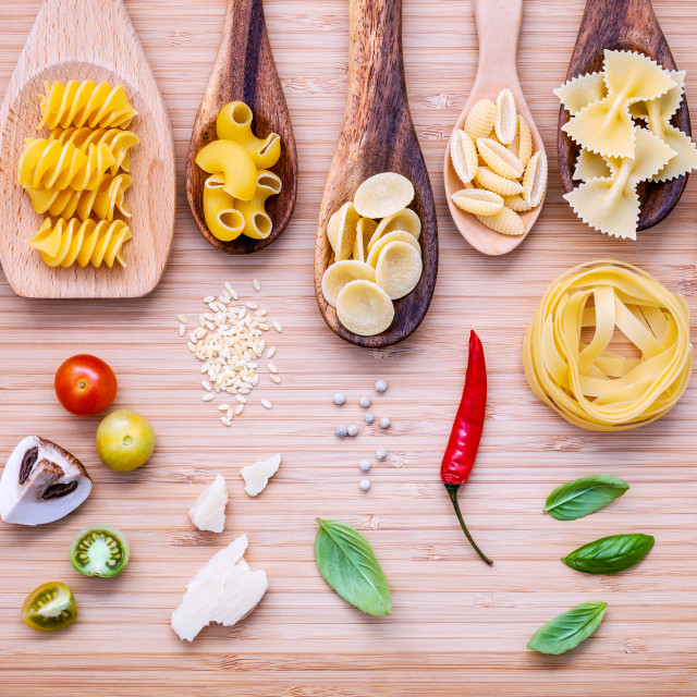 """""""Italian food concept .Various kind of pasta in wooden spoons with ingredients..."""" stock image"""