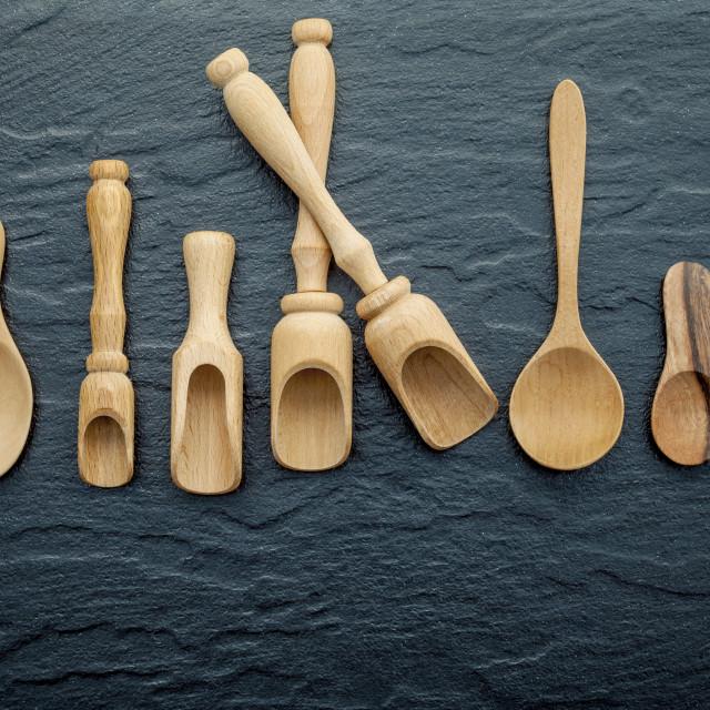 """Wooden cooking utensils border . Wooden spoons and wooden scoops on dark..."" stock image"