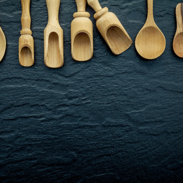 """Wooden cooking utensils border . Wooden spoons and wooden scoops on dark..."" stock image"