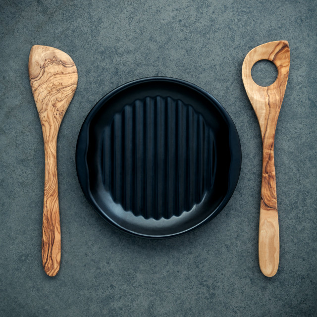 """Wooden cooking utensils wooden spoons, spatula and black plate on dark..."" stock image"