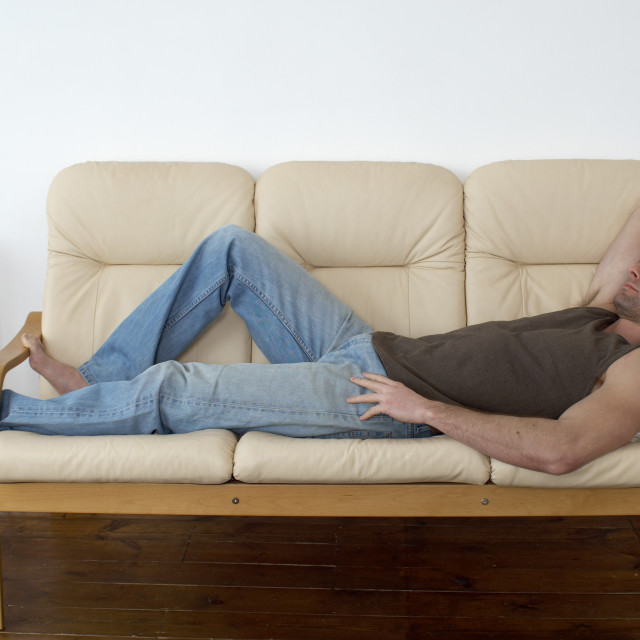 """man resting and thinking laying on a sofa, resting, taking a break"" stock image"