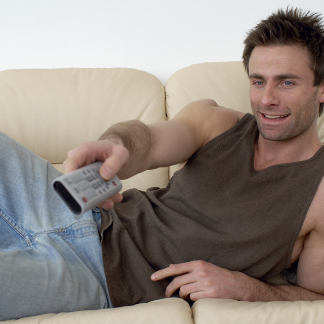 """man laying on a sofa watching television changing channels with a TV remote, zapper"" stock image"
