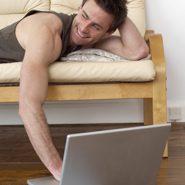 """man on sofa working on a laptop computer, home office, working from home"" stock image"