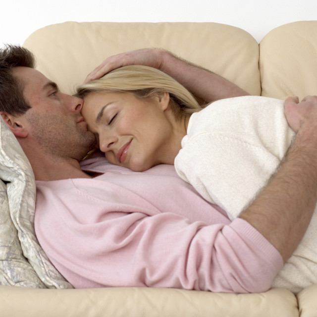 """couple cuddling up on a sofa"" stock image"