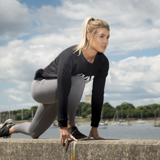 """""""fit blonde woman getting ready to run outside"""" stock image"""