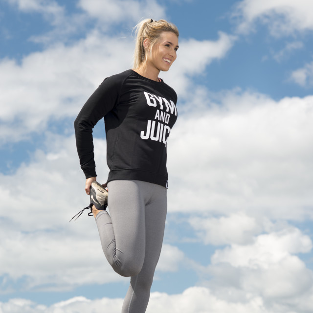 """""""fit woman doing a leg stretch while training outside"""" stock image"""
