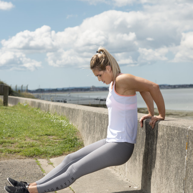 """""""fit blonde woman doing a back pressup on a wall"""" stock image"""