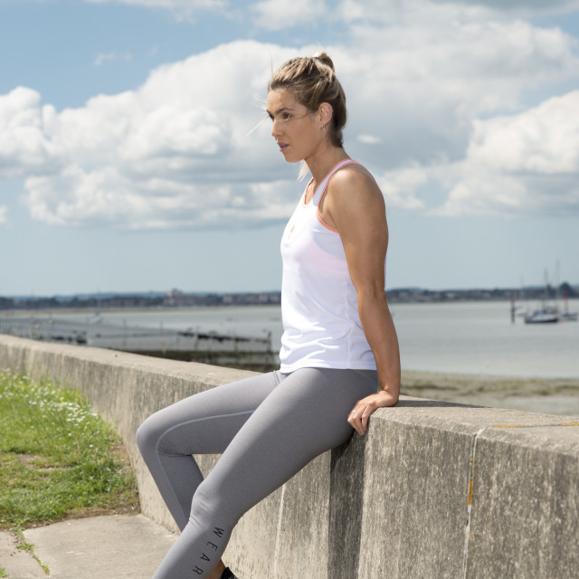 """""""fit woman sitting on a wall resting after workout"""" stock image"""