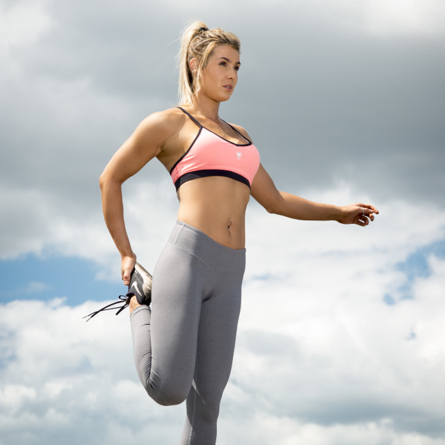"""""""fit woman wearing sports bra and leggins doing a leg stretch"""" stock image"""