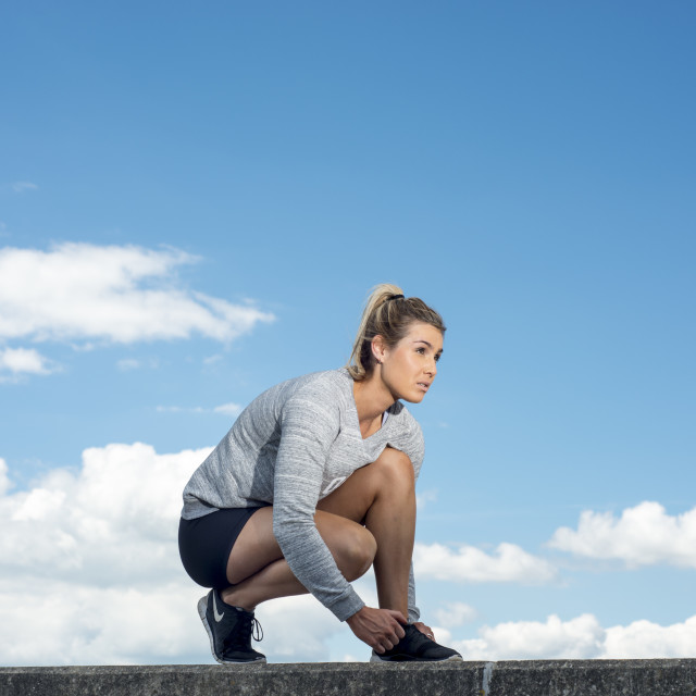 """""""fit woman tying up her shoelaces on her trainers"""" stock image"""