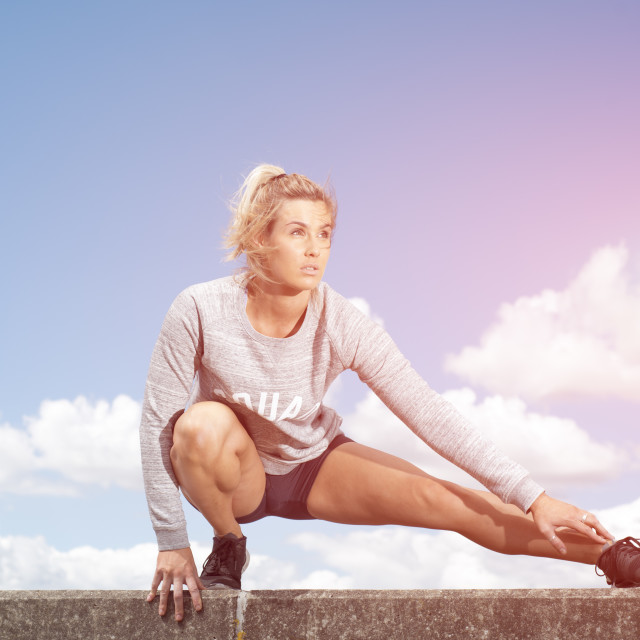 """fit woman doing a squat leg stretch"" stock image"