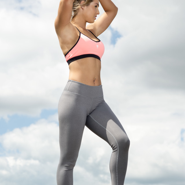 """""""fit woman wearing sports bra and leggins adjusting her hair before training"""" stock image"""