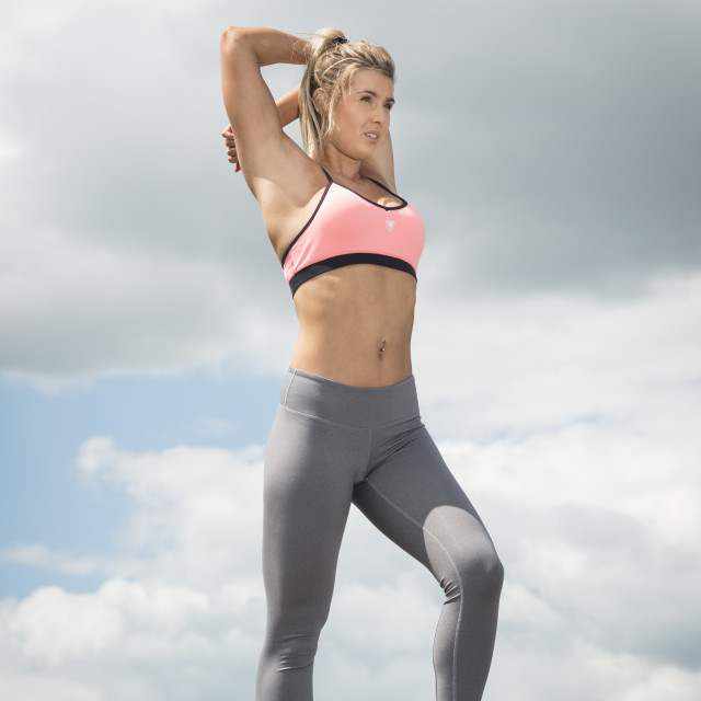 """""""fit woman wearing sports bra and leggins doing an arm stretch"""" stock image"""