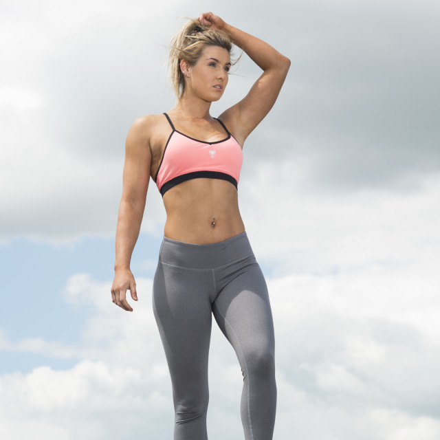 """fit woman wearing sports bra and leggins ith hands in her hair"" stock image"