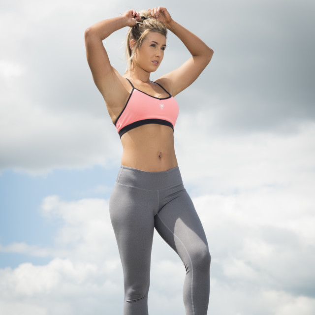 """""""fit woman wearing sports bra and leggins ith hands in her hair"""" stock image"""