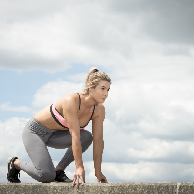 """fit woman wearing sports bra and leggins about to run"" stock image"
