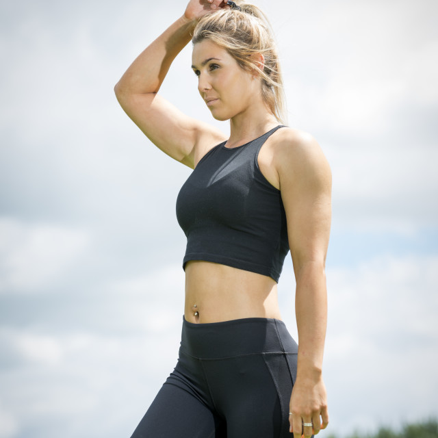 """fit blonde woman wearing black sports bra and leggins resting after exercise"" stock image"