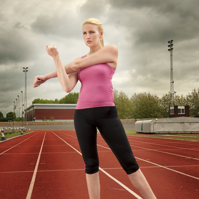 """woman stretching arms on the running track"" stock image"