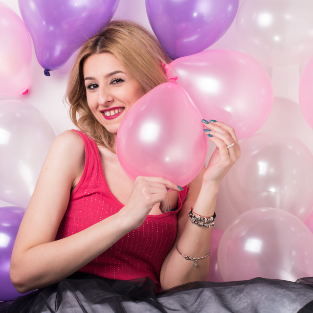 """""""young woman holding balloons and smiling"""" stock image"""