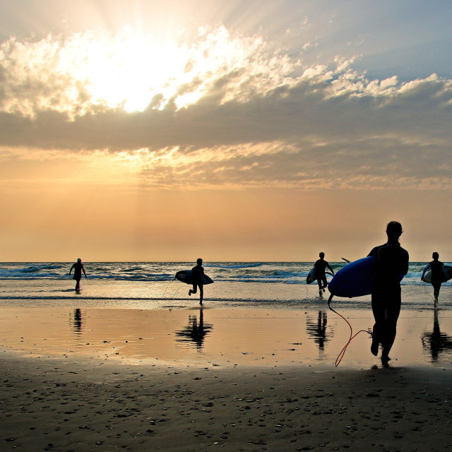 """Surfers at sunset"" stock image"