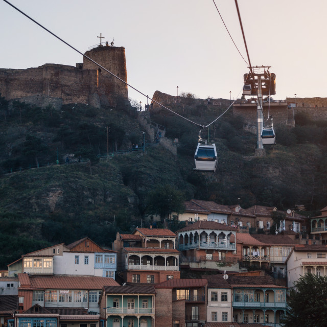 """Tbilisi Old Town and Narikala Fortress on the background of the cableway at sunset"" stock image"