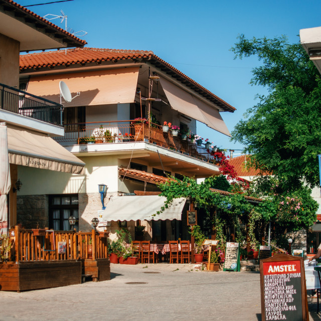 """Typical buildings on the central square with cafes and restaurants in Greek resort of Afitos, Halkidiki, Greece"" stock image"
