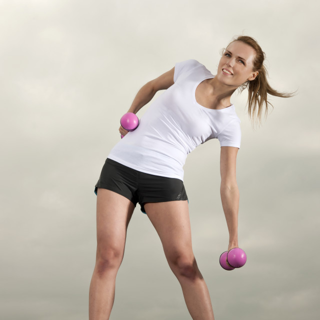 """woman lifting pink dumbbells"" stock image"