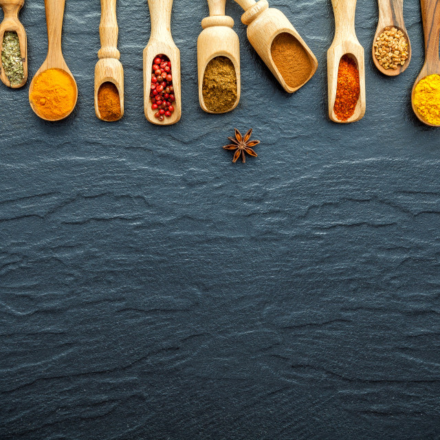 """Various of Indian spices and herbs in wooden spoons. Flat lay of spices..."" stock image"