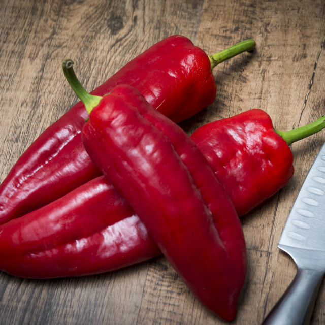 """red pointed peppers and knife on cutting board"" stock image"