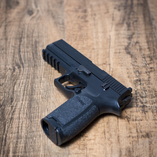"""""""A Sig P250 semi-automatic pistol on wooden surface"""" stock image"""