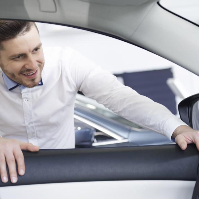 """Salesman looking inside the car in showroom"" stock image"