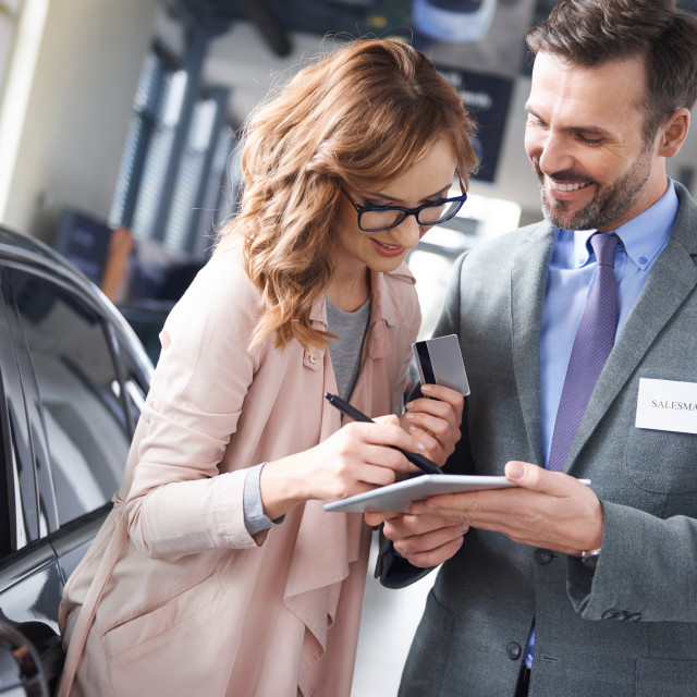 """""""Woman signing car agreement in the showroom"""" stock image"""