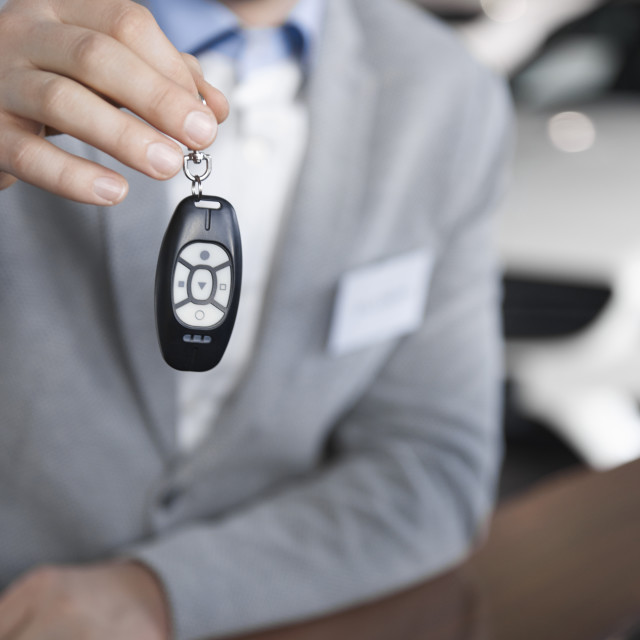 """""""Low section of car salesman with car key"""" stock image"""