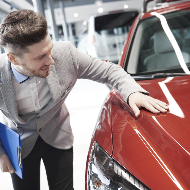 """Car salesman examining vehicle before selling"" stock image"